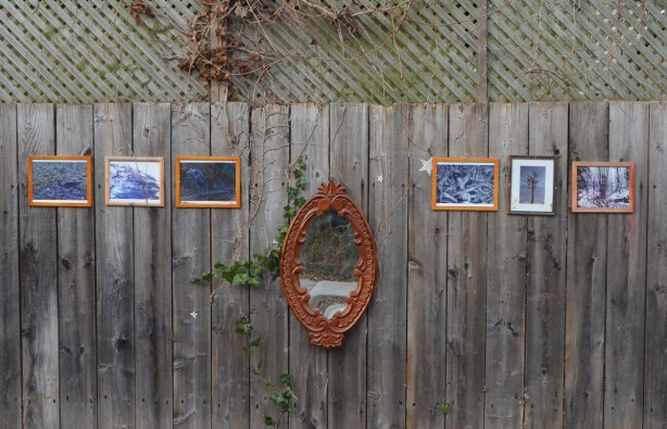 An oval mirror with an ornate wood frame is mounted on an outdoor fence, wood, three small framed pictures hang on both sides of it.