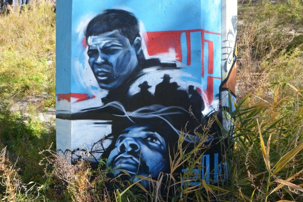 street art on the bottom of a concrete pillar, two black men. One is Mohammad Ali.