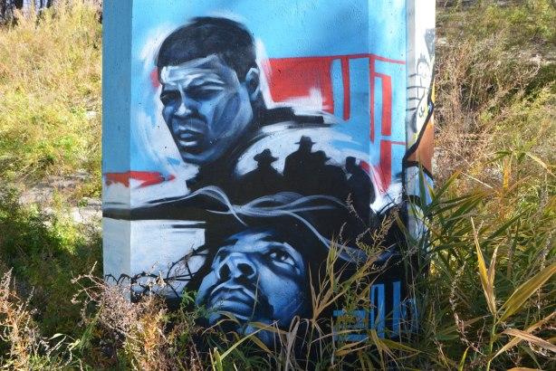 street art on the bottom of a concrete pillar, two black men. One is Mohammad Ali.