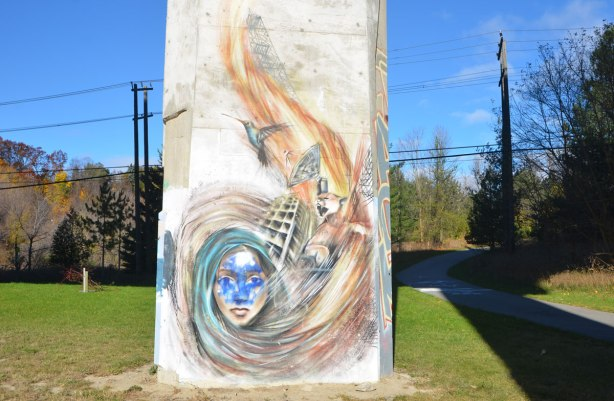street art painting on a pillar under a bridge, wispy picture of a woman with long hair, hair swirls upwards to a satelite dish and a flying bird