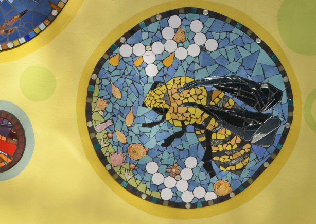 a circular mosaic picture of a bee amongst white and orange flowers on a blue background, all on a yellow wall. Part of a larger mural