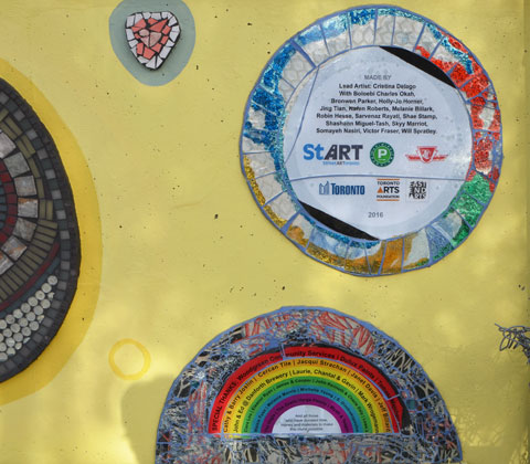 on a yellow wall, some circles made of mosaics. One is the list of people who made the whole mosaic mural and the other is a semi-circle, rainbow colours, of people of contributed to the mural