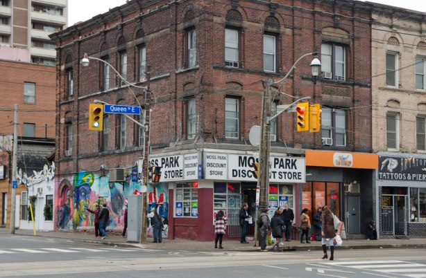 building on the corner of an intersection, Moss Park Discount Store on the corner of Queen East and Sherbourne. People on the sidewalk outside the building. 3 storey brick,