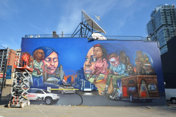 elicser painting a large mural by CP 24 parkinglot on Queen St West, showing people in the tv business - the almost completed mural