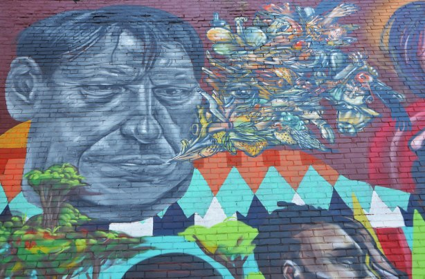part of a larger mural of elicser and Troy Lovegates, colourful people, a man's face in grey tones, many small objects coming out of his mouth - an eye, a finger with long fingernail, a cow's head, two bottle caps, a bird, and many more things.