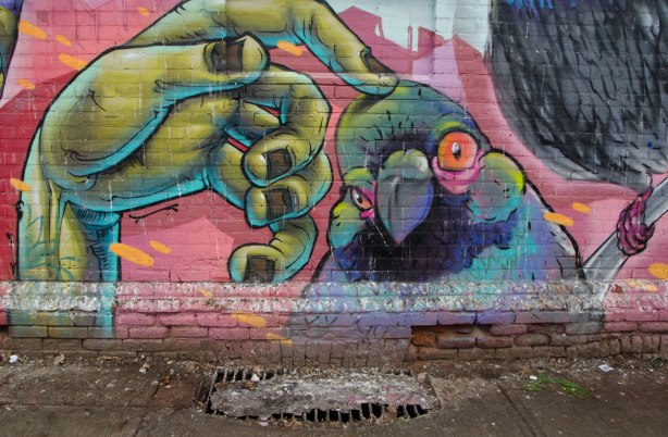 part of a larger mural, a green hand is reaching out and the forefinger is rubbing the top of a parrot's head.