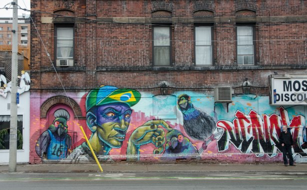 mural on the side of a red brick building, a young man in a baseball cap and three parrots. on the exterior wall of the Moss Park Discount Store.