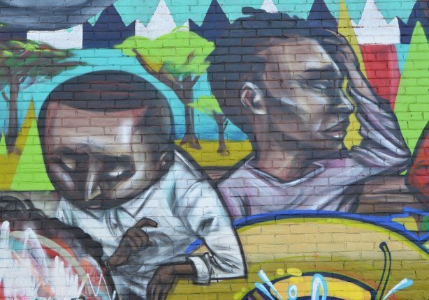 part of a larger mural, the face and heads of two young black men.