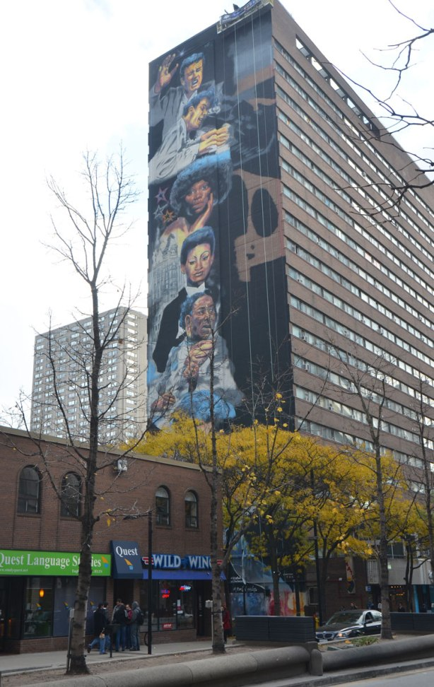 a vertical mural painted on the side of a multi storey building, the mural is a series of faces in a totem pole like arrangement