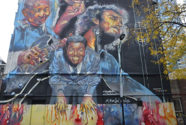 musicians and singers painted in a mural, a black man in a suit, a black man playing a guitar, a man with longish hair singing into a mic with his eyes closed.