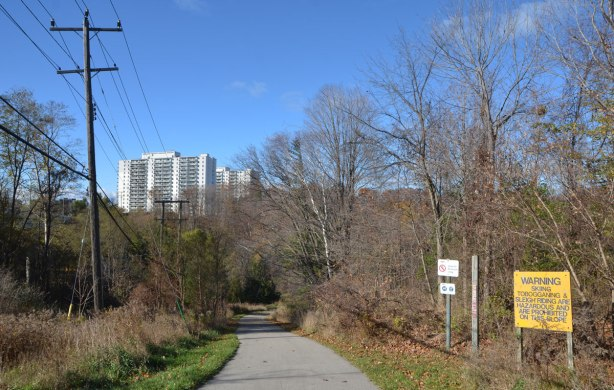 paved path leading down a hill to a ravine park, apartment buildings in the distance. Sign beside path says no skiing or sleigh riding on the slope.