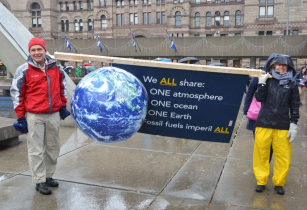 people at a rally protesting against Donald Trump as President of the USA, two people holding a banner with a 3D model of the earth with a sign that says We all share one atmosphere, one ocean , one earth, fossil fuels imperil all