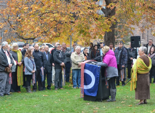 a woman in a pink jacket stands behind a podium draped with the Metis flag, speaking to a group of people outdoors at QUeens Park on Louis Riel day.