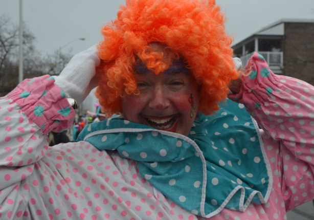 Santa Claus Parade - a man dressed as a clown with frizzy orange hair and a polka dot outfit laughs as the wind tries to blow his wig off
