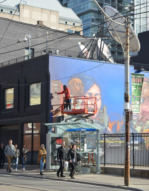 elicser painting a large mural by CP 24 parkinglot on Queen St West, showing people in the tv business - him on a lift painting above the heads of people walking past
