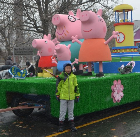 Santa Claus Parade - a young Asian boy stands beside a float featuring large sized characters from the Peppa Pig story books.