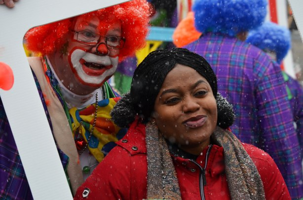 Santa Claus Parade - a black woman in a red jacket and brown scarf poses with a man in a clown costume with bright red hair.