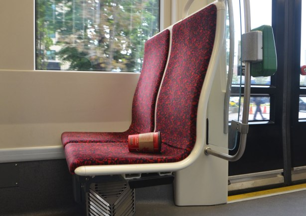 an empty red tim hortons coffee cup lies on a red TTC streetcar seat. No one is sitting there.