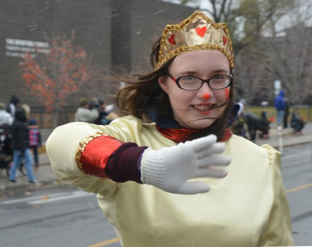 Santa Claus Parade - a young woman with a gold crown decorated with little red hearts, wearing a pale yellow dress, walking in the parade, waves at the camera