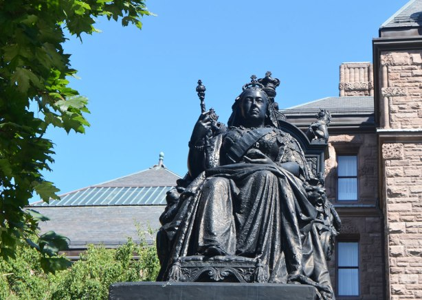 statue of Queen Victoria in bronze. She's seated, wearing crown and holding mace/staff