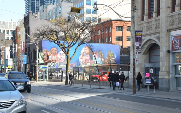elicser painting a large mural by CP 24 parkinglot on Queen St West, showing people in the tv business