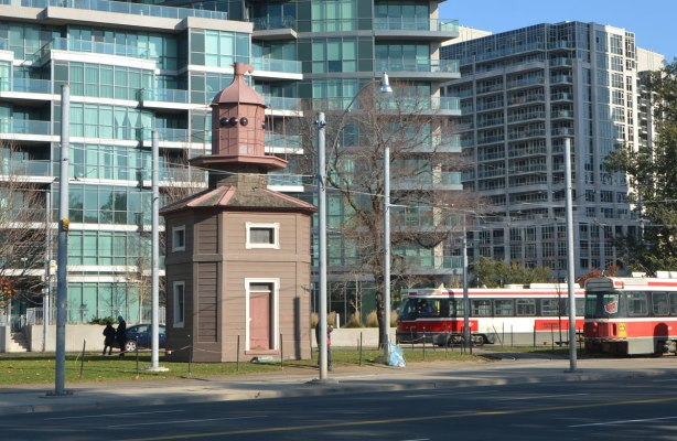 a brown structure, the Queens WHarf Lighthouse, sits on a patch of grass beside TTC streetcar tracks in front of a new condo.