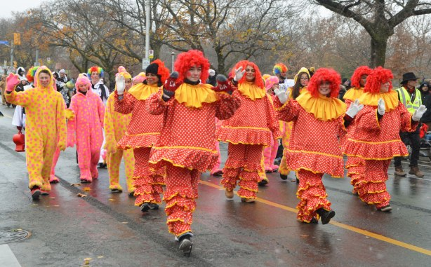 Santa Claus parade - many people dressed like raggedy Ann dolls in pink, orange and yellow with bright red hair.