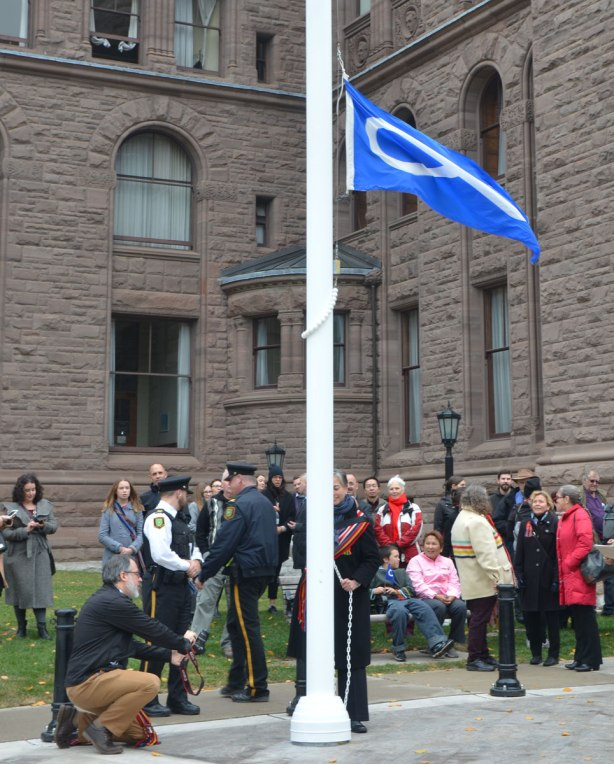 raising a blue Metis flag in front of Queens Park
