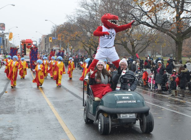 Santa Claus parade - the mascot for the Toronto Raptors basketball team is standing on the back of a golf cart driven by two people, others in costume walk behind, people standing on the sidewalks watching the parade go by