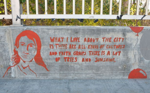 red painting on concrete wall barrier beside sidewalk on bridge over Highland Creek, in red, a girl's head and the words, What I love about the city is there are all kinds of cultures and faith groups. There is a lot of trees and sunshine.