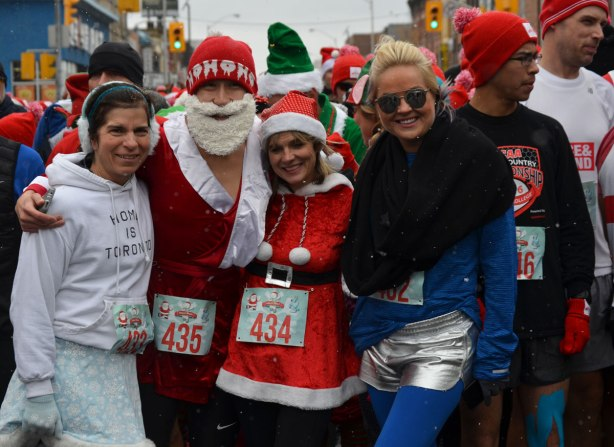 Holly Jolly Fun Run, before the Santa Claus parade, runners getting ready to start the race - group shot, woman in Mrs. Santa outfit, man in ho ho ho toque and red Santa jacket, woman in blue and another woman in a white Toronto hoodie
