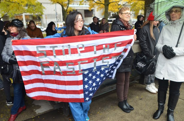 a woman holds the American flag upside down.  The words stop the fascists have been added to the flag with tape .  a protest rally at Nathan Phillips Square on a rainy day