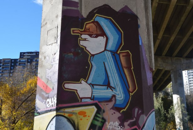 street art painting on a pillar under a bridge of a young man in a blue hoodie and brown baseball cap