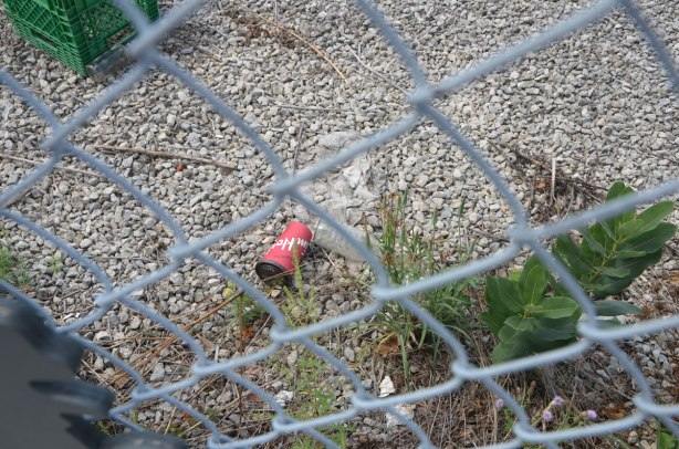 a tim hortons cup discarded onto a gravel section of a vacant lot, behind a chainlink fence