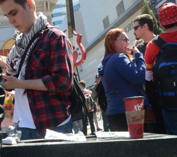a red ti hortons coffee cup sits on a ledge, people around it, all with their backs to the cup