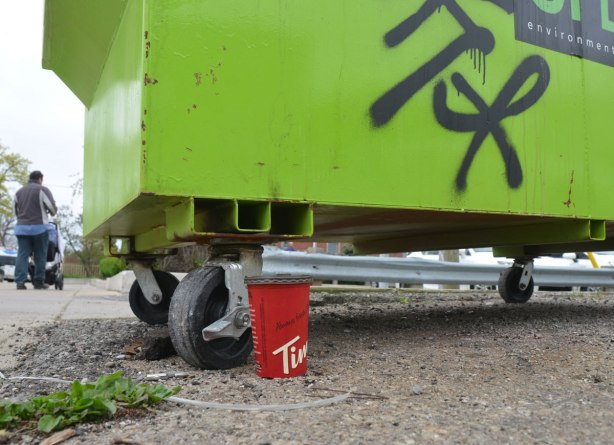 a red tim hortons cup standing on the ground beside a green rubbish bin