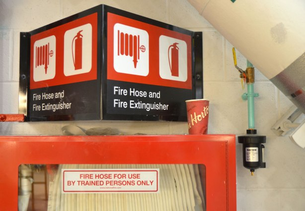 a red tim hortons cup sits on a red shelf beside fire emergency equipment