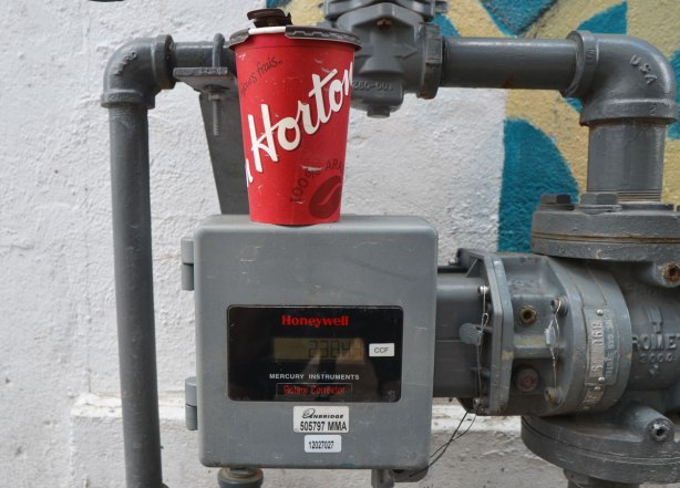 a red tim hortons coffee cup sits on top of a grey Honeywell meter outdoors