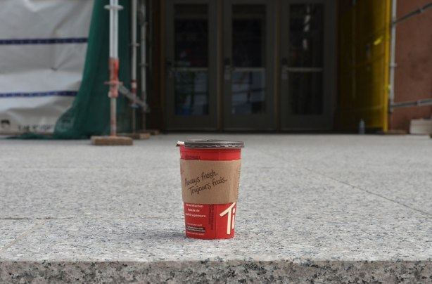 a red tim hortons coffee cup sits on the stone step in front of a double set of doors. on a street