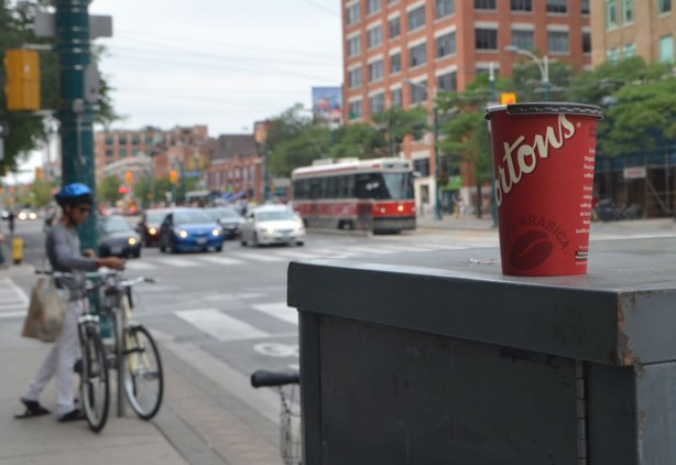 a red tim horton cup on a grey metal box on the street, traffic including a TTC streetcar are in the background