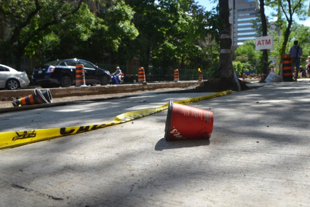 an empty red tim hortons cup lies discarded on the ground, beside yellow police tape