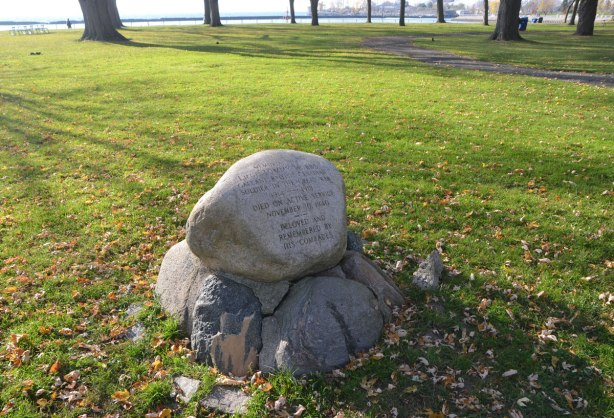 a memorial in a park made of a small pile of rocks. The top rock is inscribed, memorial to Tommy Hobbs, died 1940, in Coronation Park