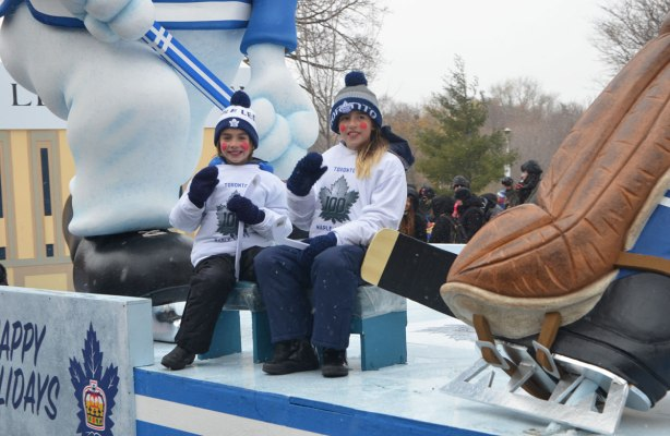 Santa Claus parade - two kids wearing Toronto Maple Leafs sweatshirts and toques sitting on a float with a loarge replica of Carlton the Leafs mascot. The skate and end of the stick of a large statue of a hockey player is also in the picture.