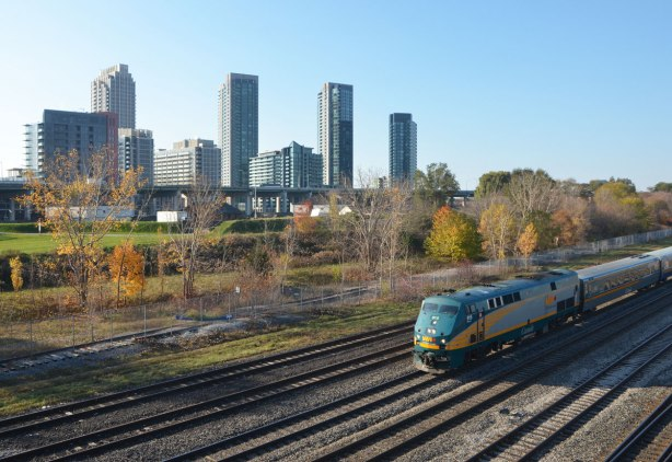 a VIA Rail train passes by on one set of many tracks, in the background is Fort York and then a series of new condo buildings.