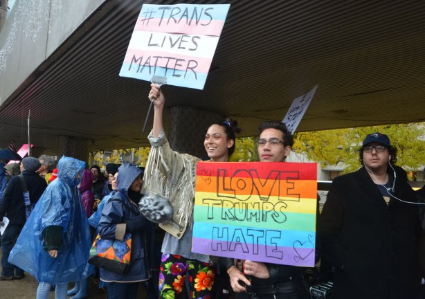 people at a rally protesting against Donald Trump as President of the USA, a young couple with placars. One says Trans lives matter and the other is painted in rainbow stripes with the words Jove Trumps Hate written on it.