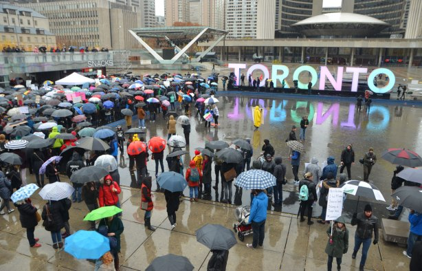 people at a rally protesting against Donald Trump as President of the USA, a wet rainy day, looking out over Nathan Phillips Square with city hall, the 3D Toronto sign and many umbrellas
