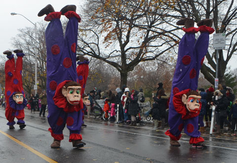Santa Claus parade - three people walking in the parade with costumes that make it look like they are clowns that are walking on their hands, people on the sidewalk watching the parade.
