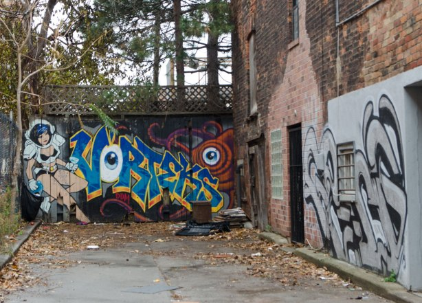 two murals in an alley. At the end, on a fence is a mural by vorteks, text with his signature using an eyeball for the letter O. An orange creature with an eye, most of which is behind the text, as well as a scantily clad woman who looks like a superhero.