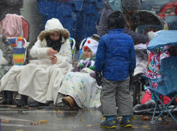 Santa Claus parade - a young boy stands with his back to the camera. He is in front of people sitting on the sidewalk waiting for the parade to start. It is snowing and people are all bundled up. In this case, a mother and her daughter are dressed in white jackets and have a white blanket over their knees.