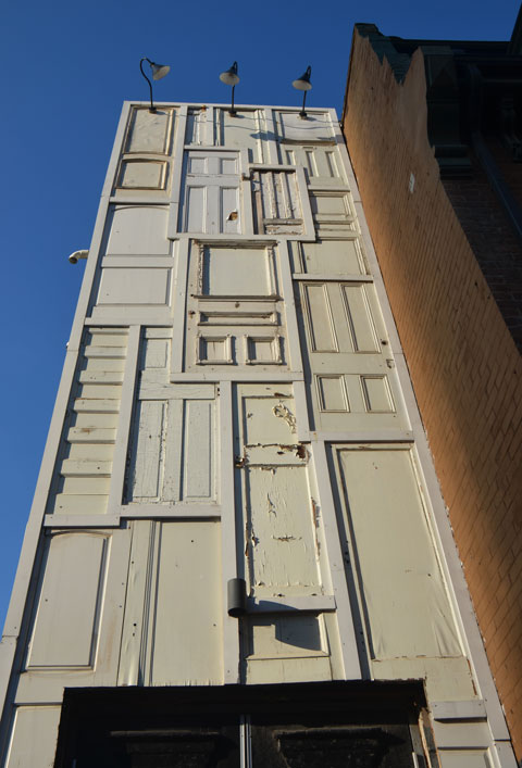 a tall narrow wall about three storeys high made of old white doors.